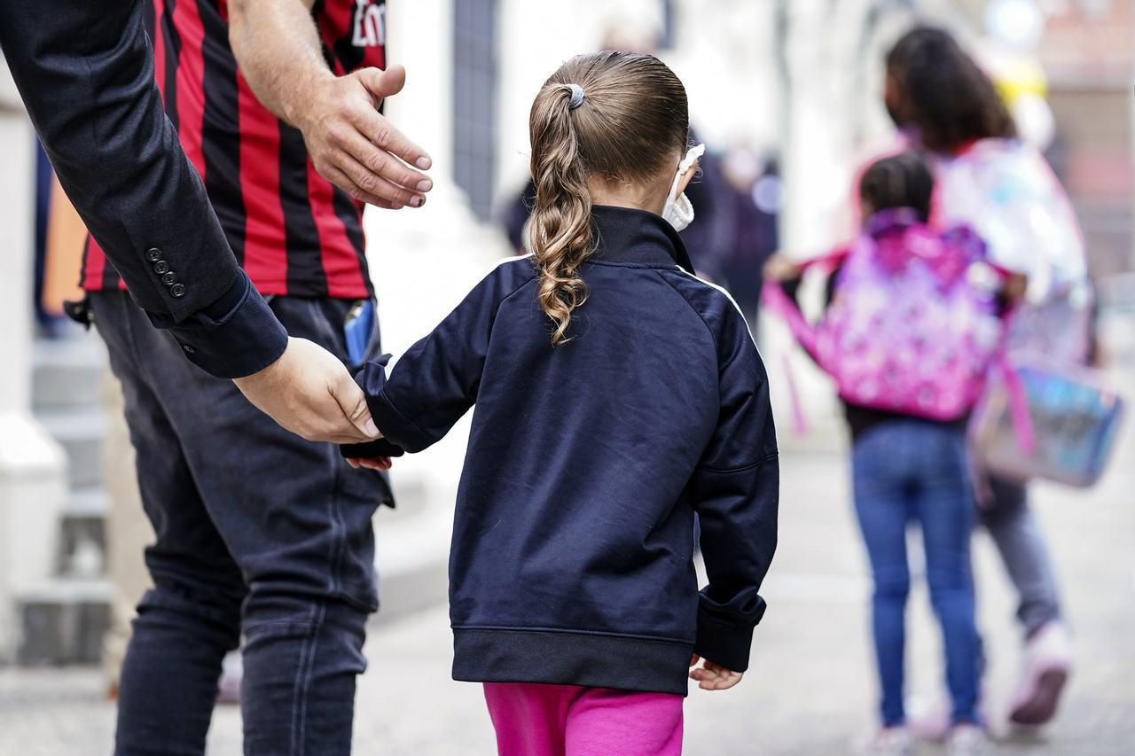 紐約市家長29日把子女送到學校上課。(美聯社)