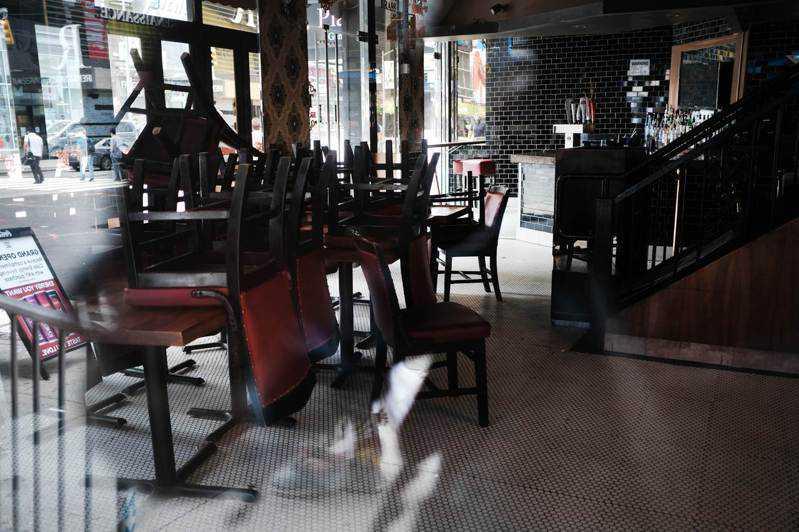 曼哈顿一间餐馆内空无一人,椅子叠在餐桌上已长达数月;纽约市餐馆终于可从9月30日...
