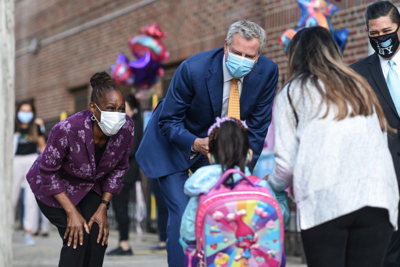 纽约市公校校长工会投票通过对市长白思豪和市教育总监卡兰扎的不信任案;图为白思豪(中)与卡兰扎(右)日前欢迎复课返校的学童。(市长办公室提供)