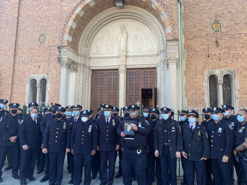 62分局警员手捧雷大卫的遗照,为他举行悼念仪式。(记者黄伊奕/摄影)