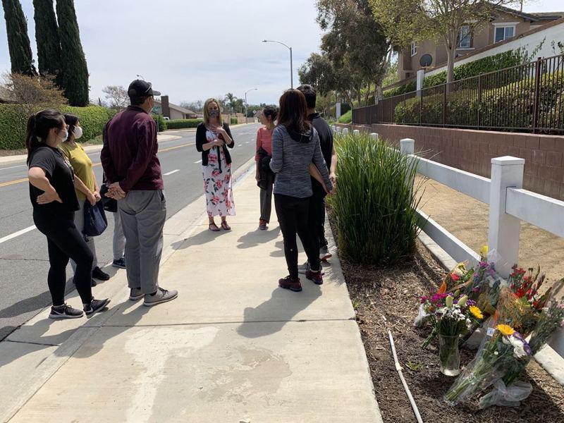 一名附近白人居民(中)送上鮮花,並向受害者親友詢問案發過程。(記者啟鉻/攝影)