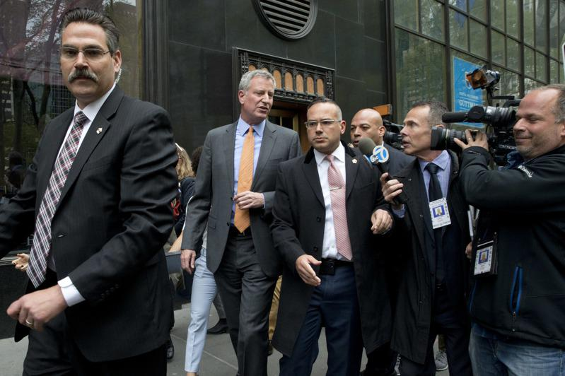 市调查局报告指出,市长白思豪和家人涉嫌滥用市警总局资源;图为白思豪与他的市警安保人员在一起。(美联社)