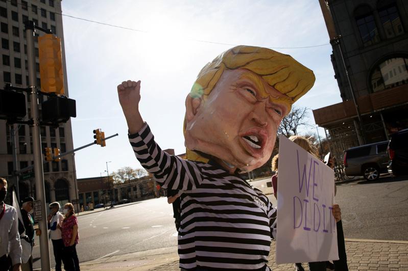 密西根州底特律一位市民,7日在街头装扮成川普穿囚衣的样子。(路透)