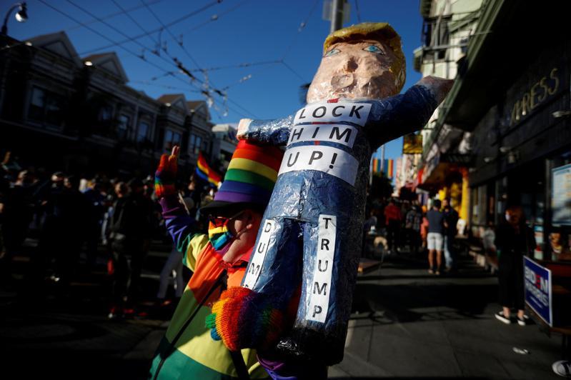 加州旧金山民众7日上街庆祝白登当选总统,还制作了火箭人玩偶嘲讽川普。(路透)