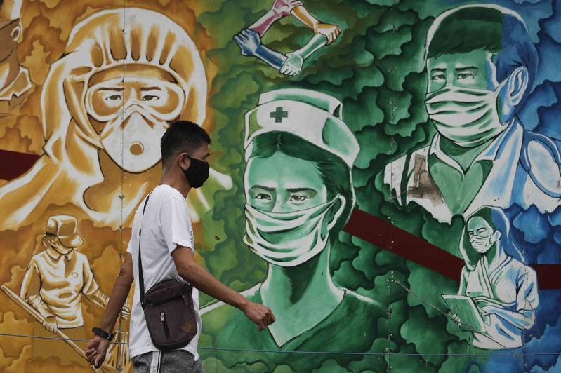 菲律賓,一市民走過畫滿醫護畫像的壁畫。(美聯社)