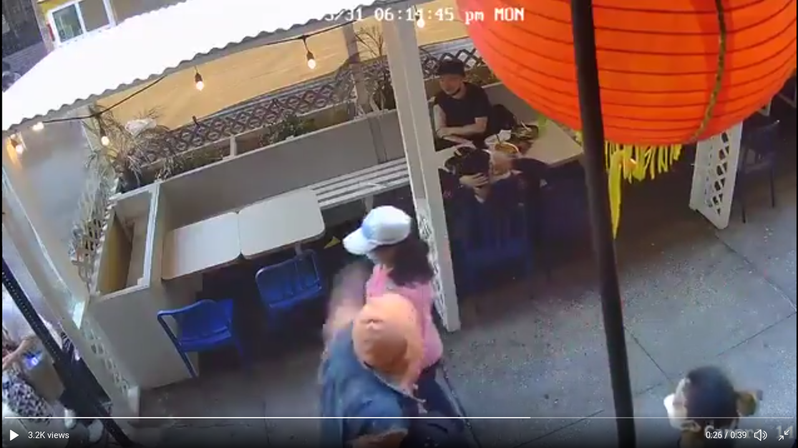 非洲裔男嫌突然朝著迎面走來的婦人揮拳打臉。(截自現場監視器畫面)
