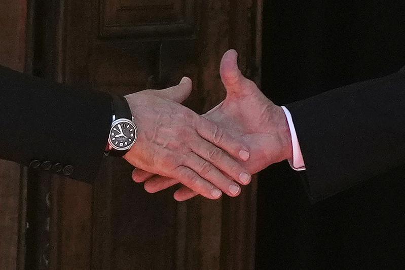 兩人見面後在會談場所門外握手,左為普亭,右為拜登。(美聯社)