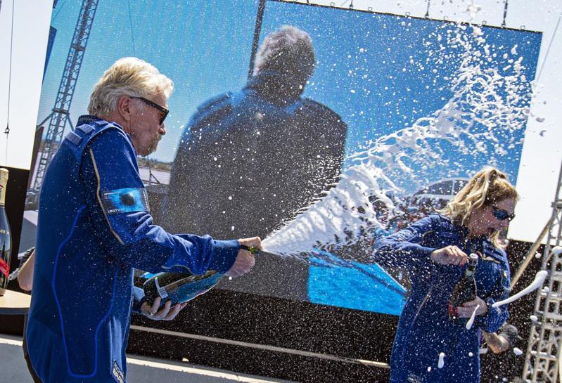 英國億萬富豪布蘭森(左)今天搭乘自家太空船上太空一遊後平安返回地球。(美聯社)